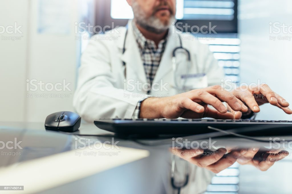 Profesional médico mediante teclado de la computadora en la clínica. - foto de stock
