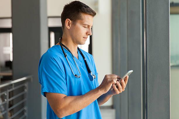medical professional using smart phone stock photo