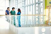 Three diverse medical professionals talking in modern hospital corridor