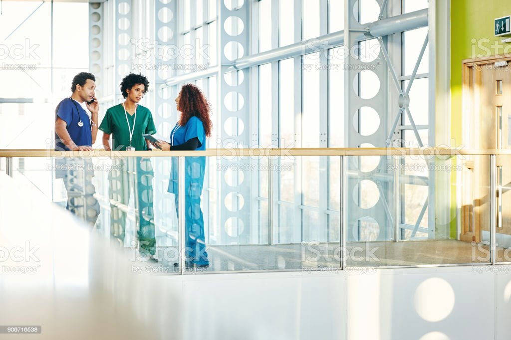 Mediziner sprechen in modernen Krankenhausflur – Foto