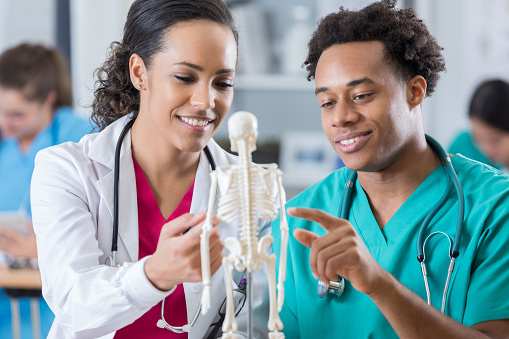 African American male medical student discusses skeletal system with medical school professor.