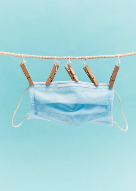 Cтоковое фото Medical protective mask hanging on a rope isolated on pastel blue background