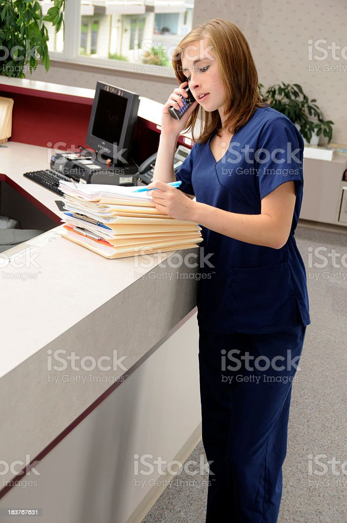 A medical receptionist on the phone looking at files stock photo