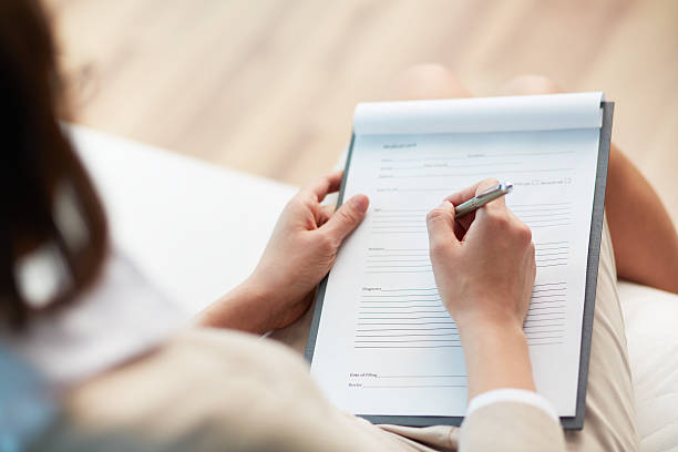 Medical record Female counselor writing down some information about her patient application form stock pictures, royalty-free photos & images