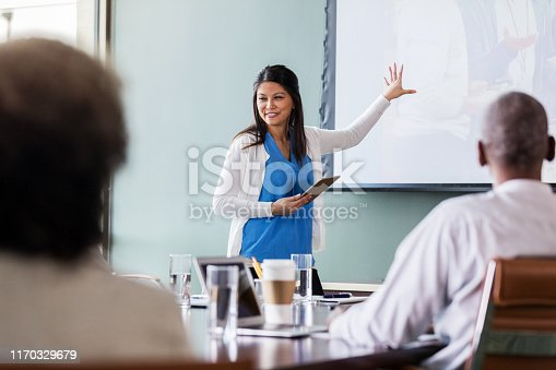 While gesturing toward a projected image of a doctor, a medical sales rep discusses a new drug or product. She is holding a digital tablet.