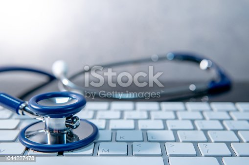 istock Medical science technology concept. Blue stethoscope on white modern keyboard on doctor desk. Health and wellness background. Global healthcare business. Computer antivirus protection 1044227478