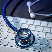 istock Medical science technology concept. Blue stethoscope on white modern keyboard on doctor desk. Health and wellness background. Global healthcare business. Computer antivirus protection 1132079068