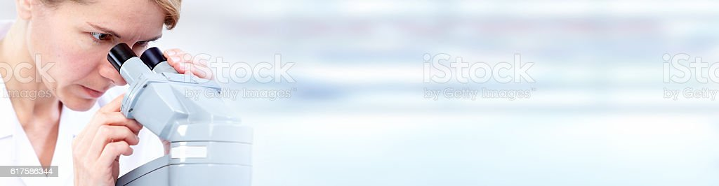 Medical scientist woman with microscope. stock photo