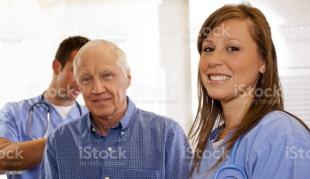 Medical: Senior man being checked by doctor, nurse in foreground royalty-free stock photo
