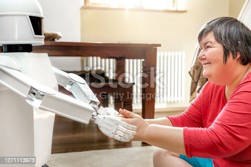 istock medical service robot is giving a mentally disabled woman the hand, learning with an artificial  intelligence 1271113973