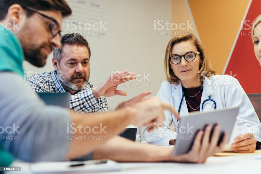 Medical staff during morning briefing in boardroom stock photo