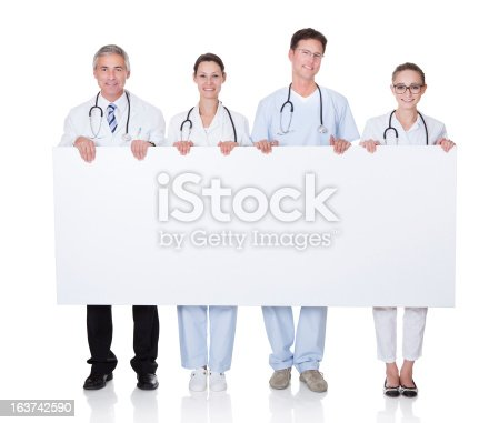 1048561866 istock photo Medical staff holding up a white banner 163742590