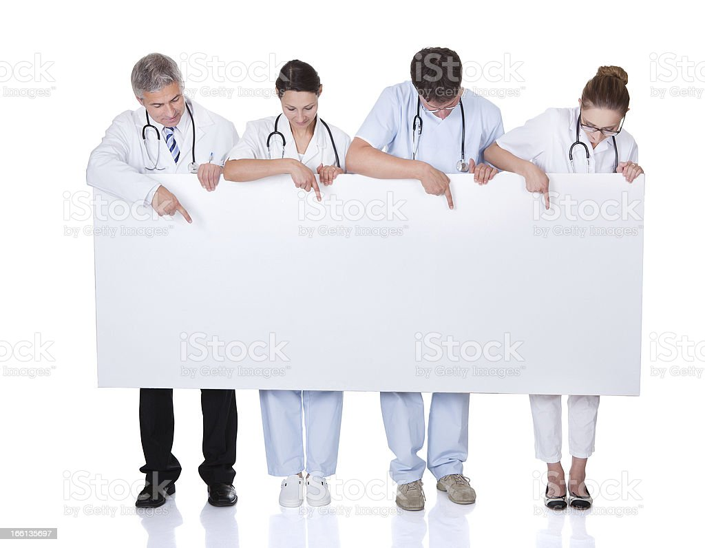 Medical staff holding up a white banner stock photo