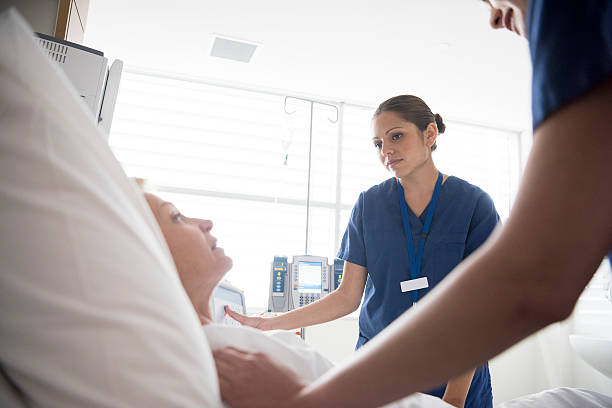 medical staff looking after patient in hospital, close up - australian nurses stock photos and pictures
