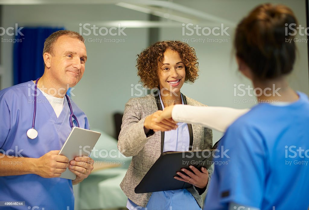 a mature hospital doctor is chatting with a team of fellow medical...