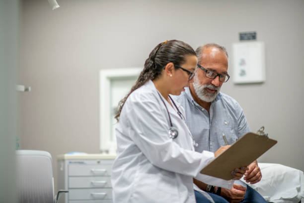 Medical Staff Prepare Their Infectious Control Attire stock photo A female doctor sits next to an elderly male patient during the Covid-19 outbreak.  They are reviewing the patient chart together. medical research stock pictures, royalty-free photos & images