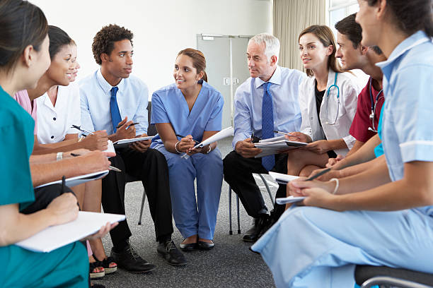 Medical Staff Seated In Circle At Case Meeting stock photo