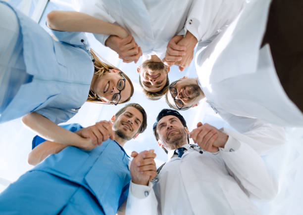 Medical staff standing in a circle at a meeting stock photo