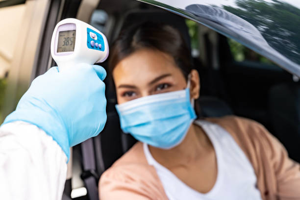 Medical staff take temperature drive thru service stock photo