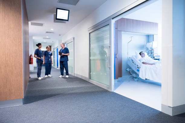 medical staff talking in corridor, patient in bed in ward - australian nurses stock photos and pictures