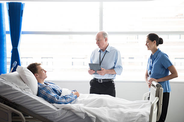 medical staff talking to male patient in hospital bed - australian nurses stock photos and pictures
