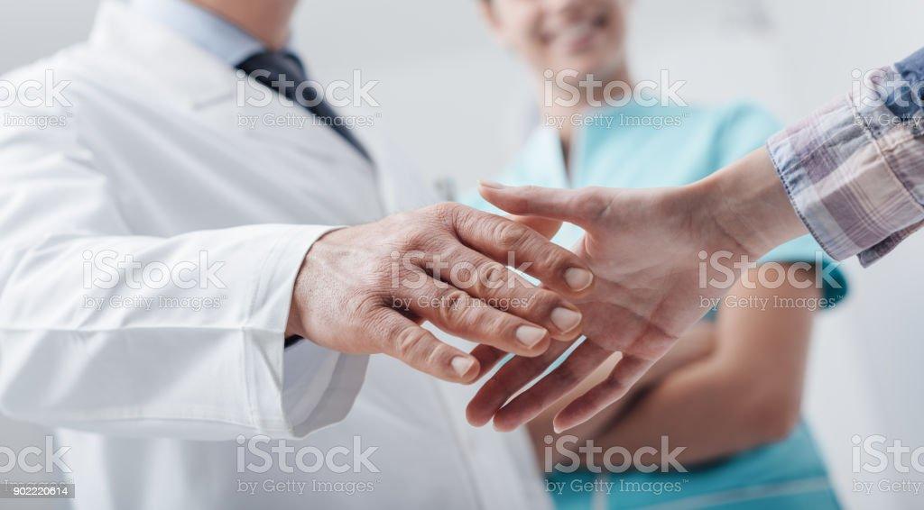 Equipe médica, congratulando-se um paciente foto royalty-free