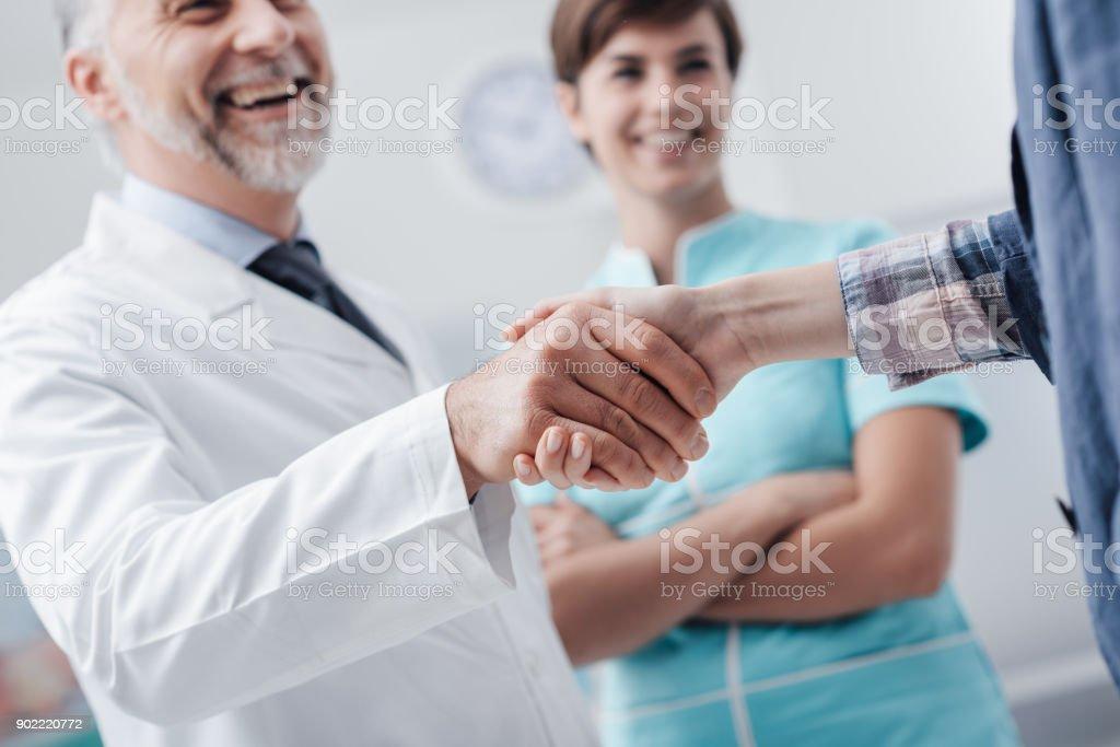 Equipe médica, congratulando-se um paciente - foto de acervo