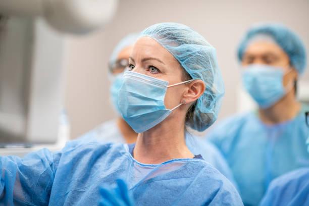 medizinisches personal arbeitet zusammen in full infectious control kleidung stockfoto - pandemie stock-fotos und bilder