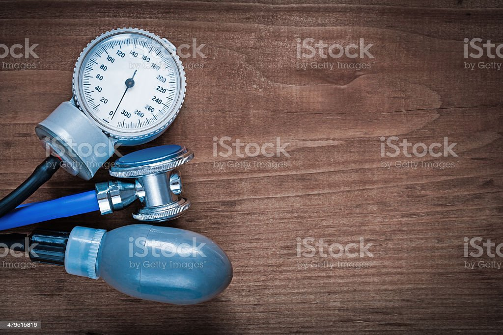 Medical stethoscope and blood pressure monitor on vintage wooden stock photo