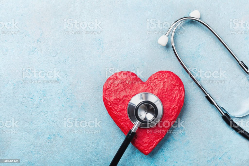 Medical stethoscope and red heart on blue background top view. Healthcare, pulse, heartbeat, medicare and cardiology concept. stock photo