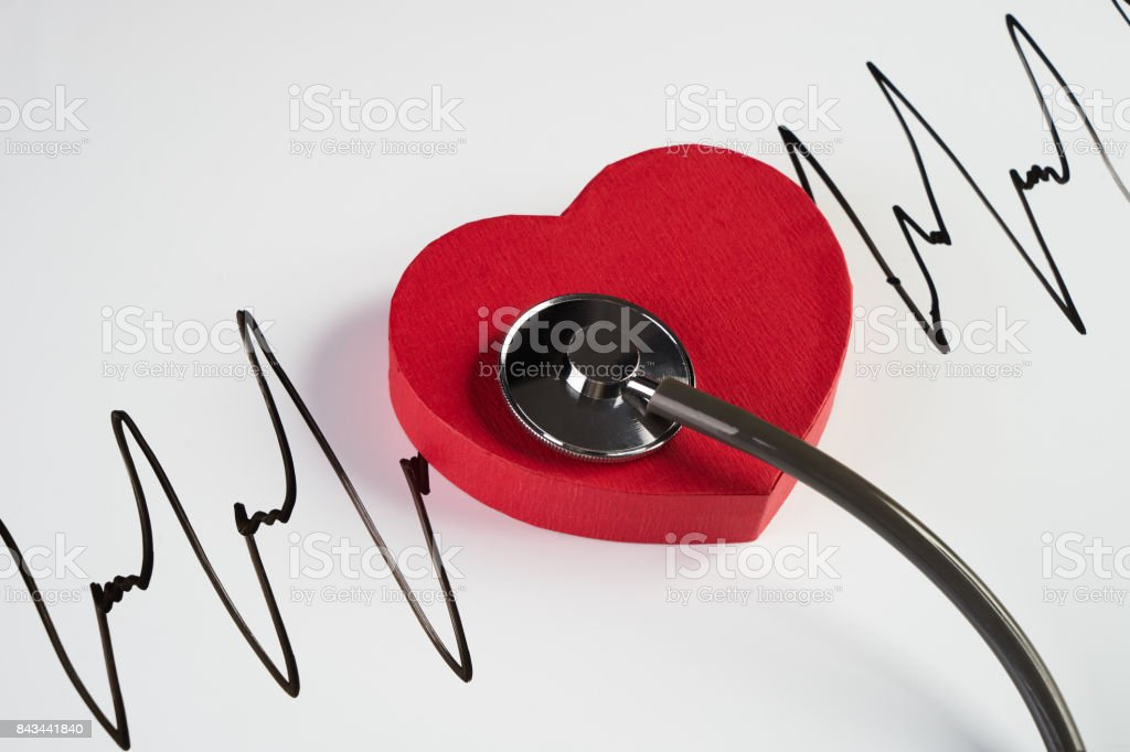 Medical stethoscope and red heart with cardiogram stock photo