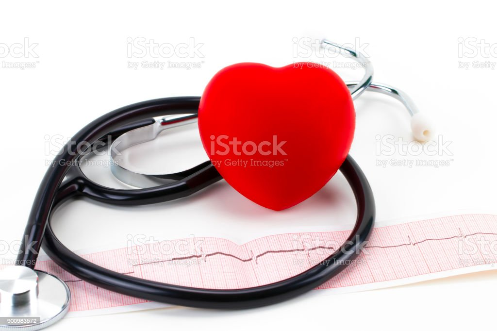 Medical stethoscope and red toy heart lying on cardiogram chart closeup. Medical help, prophylaxis, disease prevention or insurance concept. Cardiology care,health, protection and prevention stock photo