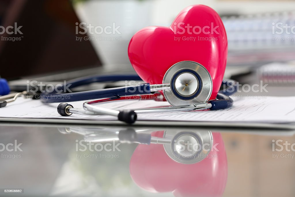 Medical stethoscope head and red toy heart lying on cardiogram stock photo