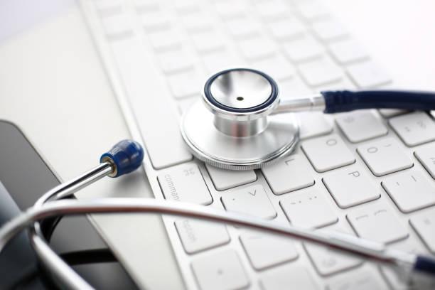 Medizinischestethoskop Kopf liegt auf silber Tastatur am Arzt Büro Arbeitstisch – Foto
