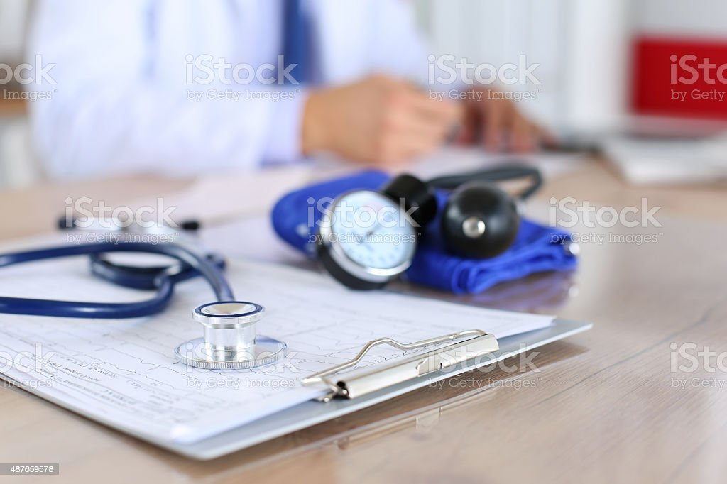 Medical stethoscope lying on cardiogram chart closeup Medical stethoscope lying on cardiogram chart closeup while medicine doctor working in background. Cardiology care,health, protection, prevention and help. Healthy life or insurance concept 2015 Stock Photo