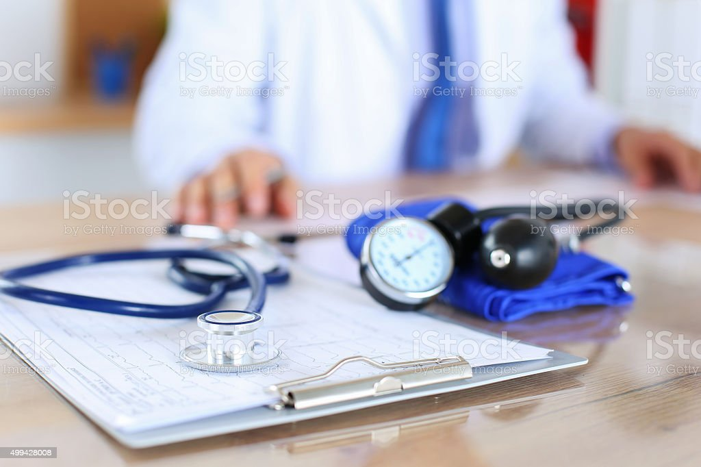 Medical stethoscope lying on cardiogram chart closeup stock photo