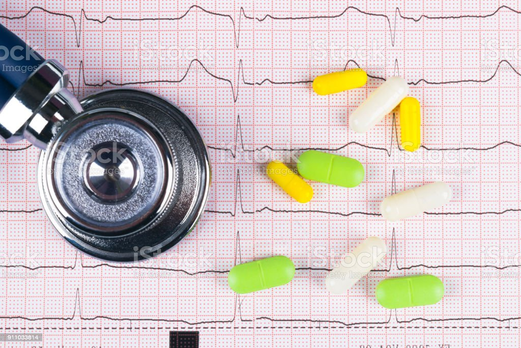 Medical Stethoscope Lying On Cardiogram Chart With Pile Of Pills