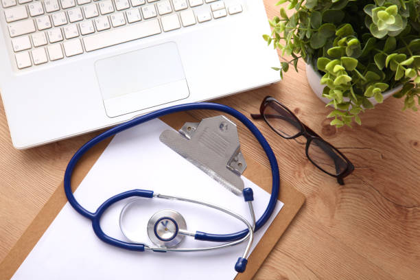 A medical stethoscope near a laptop on a wooden table, on white – zdjęcie