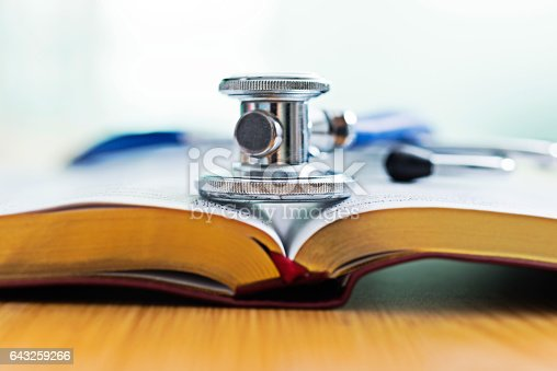 Medical stethoscope on a opened book.