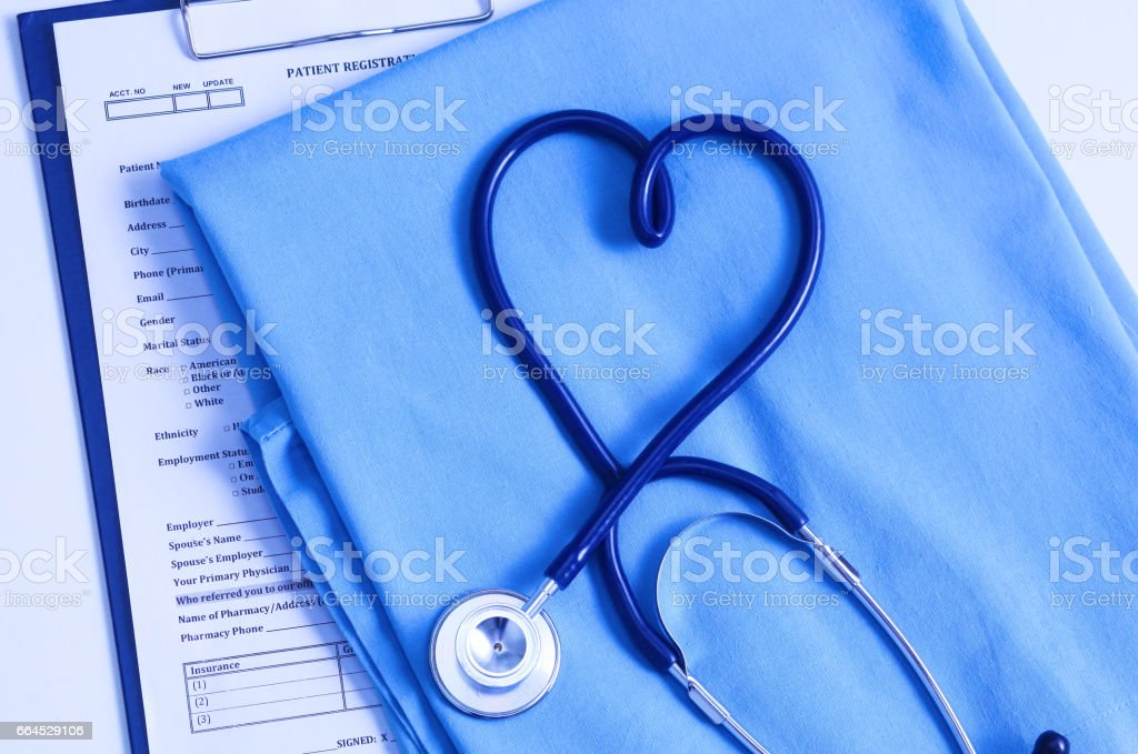 Medical stethoscope twisted in heart shape lying on patient medical history list and blue doctor uniform closeup. Medical help or insurance concept. Cardiology care, health, protection and prevention royalty-free stock photo