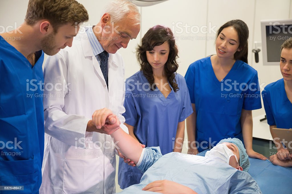 Medical students and professor checking pulse of student stock photo