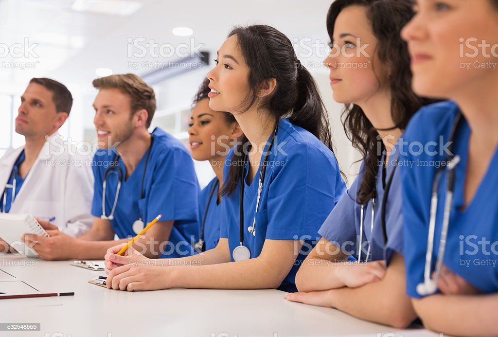 Medical students listening sitting at desk stock photo