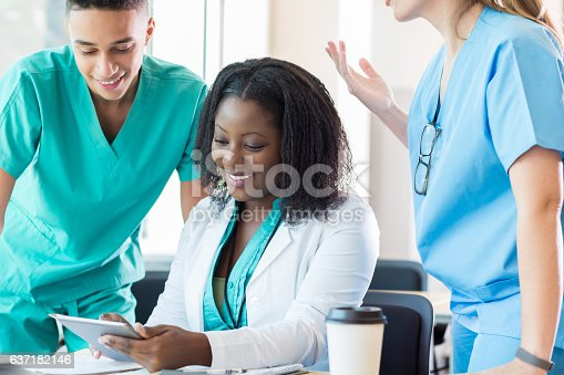 istock Medical students look at something on digital tablet before class 637182146