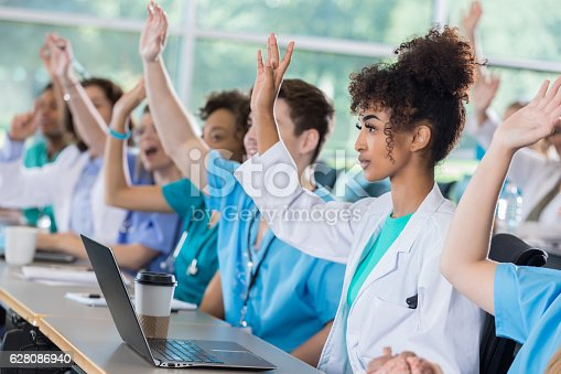 600055398 istock photo Medical students raise hands in class 628086940