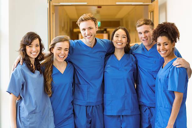 étudiants en médecine souriant à la caméra - vêtements professionnels hospitaliers photos et images de collection
