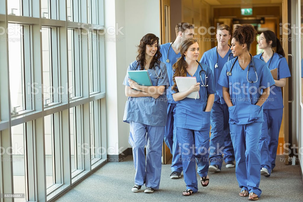 Medical students walking through corridor stock photo