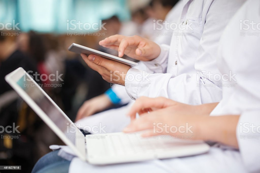 Medical students with pad and laptops in auditorium stock photo