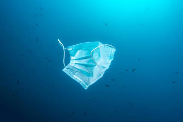medical surgical mask floating underwater sea trash stock photo