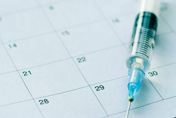 Medical syringe on calendar background stock photo
