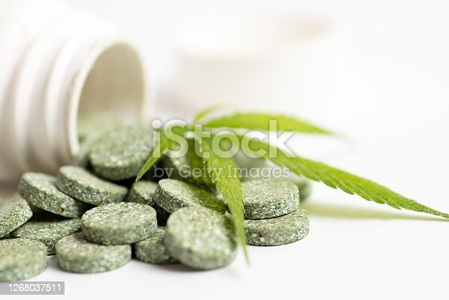 Green medical tablet pills with infused cannabis oil and marijuana leaves closeup
